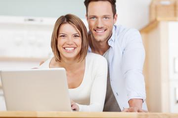 junges lachendes paar mit laptop zu hause