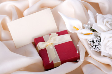 Holiday gift with a bouquet of the bride and a card on a gentle