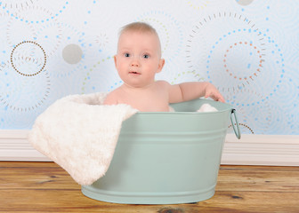 bright baby boy sitting in washtub