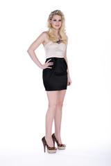 Blonde Frau mit tollen Schuhen posiert schmunzelnd Fashion