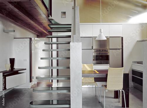 cucina moderna in mansarda e scala di vetro\