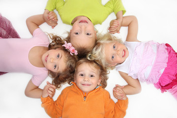 Funny kids lying down on the floor in cross shape
