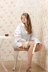 A girl in a man's shirt and stockings sitting on a chair