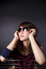 female model pose with cool action with sunglasses on chair.