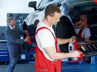 Master mechanic inspecting a break of a car on a service lift
