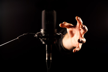 Hand greift nach Mikrofon