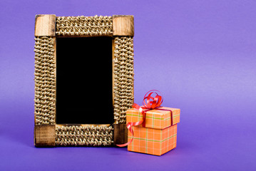 Wooden photo frame and orange gift box with red ribbon on blue b