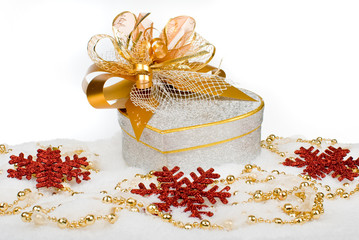 Christmas silver heart gift box with golden ribbon in snow on a