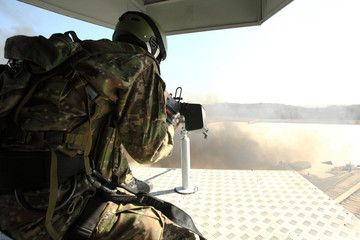 Soldier in helicopter shooting