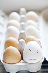 Angry faced egg in a carton