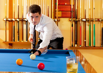 Billiard winner handsome man playing with cue and balls