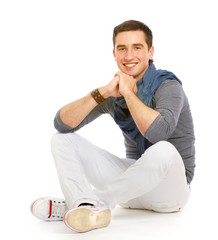 A full-length portrait of a young smiling guy sitting