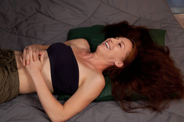 Pretty woman with long hair, laying down laughing