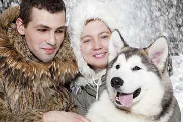 Young couple with a malamute dog