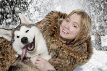 Portrait of young woman with malamute