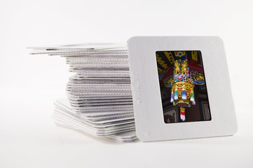 A pile of old slide photos, with a photo of a Chinese decoration