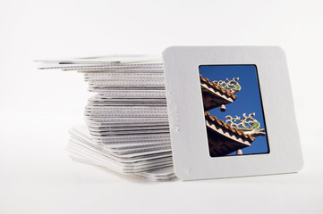 A stack of old slide photos, with a photo of a temple roof