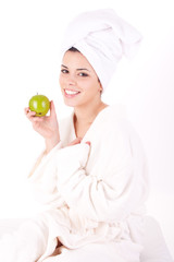 Beautiful young woman in a white spa bath robe eating a apple