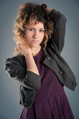 Portrait of beautiful curly girl posing against grey background.