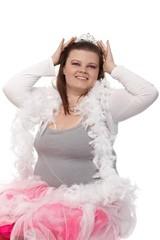 Fat woman daydreaming in tiara smiling