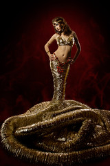 Beautiful woman in fantasy dress. Snake fashion dress stylish. A