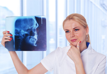 Portrait of attractive woman doctor looking at X-ray results of