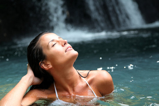Beautiful woman enjoying bathing near natural waterfall