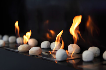 White circular stones and beautiful yellow flames in fireplace