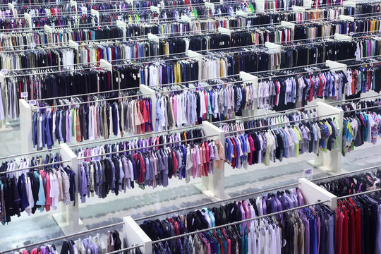 Big clothing store, many rows with hangers with skirts