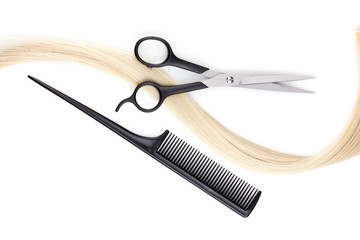 Shiny blond hair with hair cutting shears and comb isolated