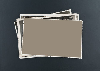 Stack of old photos on elegant, black leather