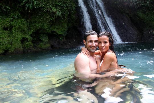 Happy couple bathing near waterfall in island