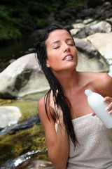 Beautiful young woman applying hair conditioner sitting by river
