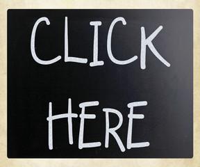 """Click here"" handwritten with white chalk on a blackboard"