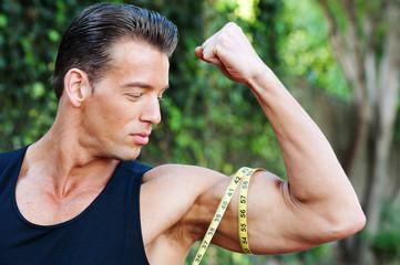 Muscular man measuring bicep