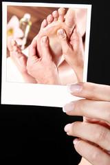 Hand zeigt Foto mit SPA Fuß Massage