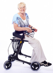 happy elderly lady sitting on a  walker for disabled people