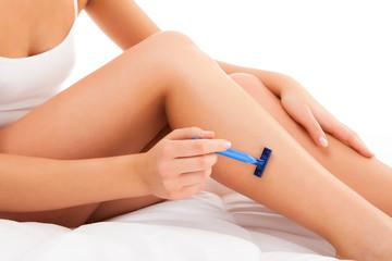 Woman shaving legs sitting on white background