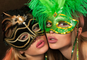 Two beauties posing sexy in lingerie and carnival masks