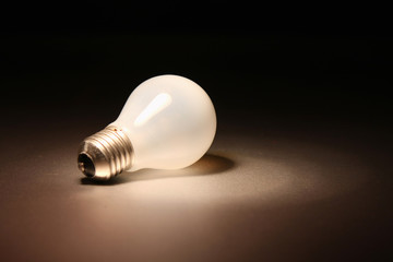 Background with lit lightbulb. Isolated on black