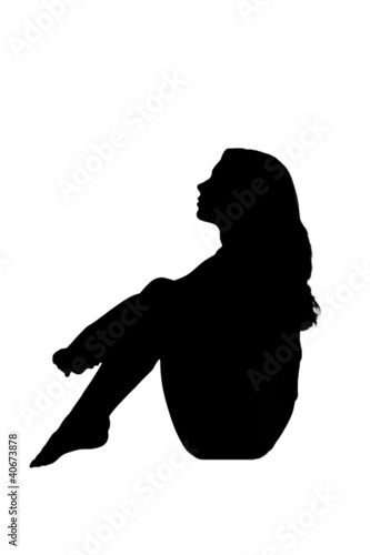 silhouette in shadow of a young woman sitting sad pensive