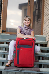 Happy woman with luggage in front of home