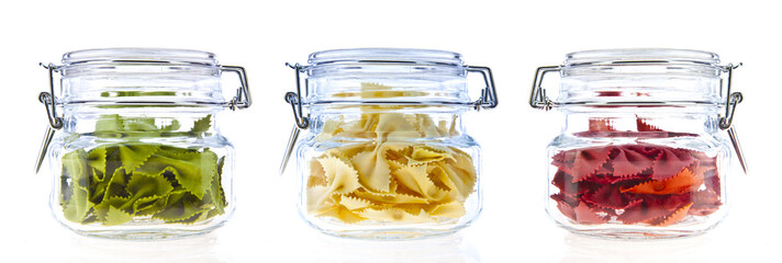 Jars of coloured pasta isolated on white