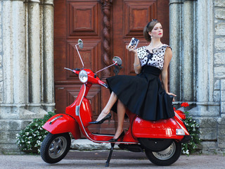 A young woman posing in a dress behind a scooter
