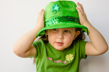 Pretty little girl tries on a fancy hat for St. Patrick's Day