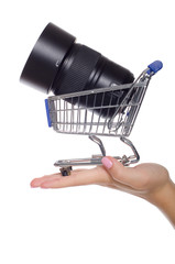 Camera lens in shopping trolley on the palm