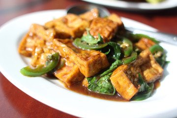 Plate of tofu with basil and chili pepper sauce.