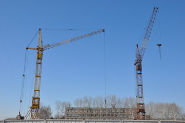 Two construction cranes on site.