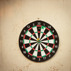 Dartboard hanging on an old, shabby wall (image with copy space)