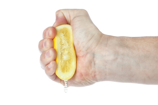The hand squeezes a lemon. On a white background.